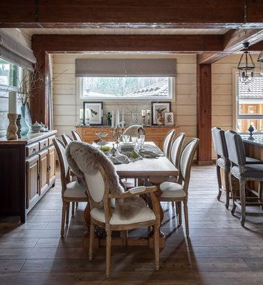 Столовая в доме из клееного бруса. Фальшбалки выполнены из брашированной сосны. Стол из массива дуба, стулья со спинками в форме медальонов.