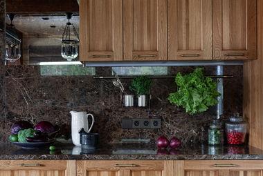 Кухня выполнена из дуба, столешница и фартук из мрамора Emperador Dark, стена за кухней отделана состаренным зеркалом.