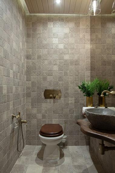 Гостевой туалет в загородном доме. Плитка CIR Serenissima. Столешница из слэба карагача. Раковина из речного камня.